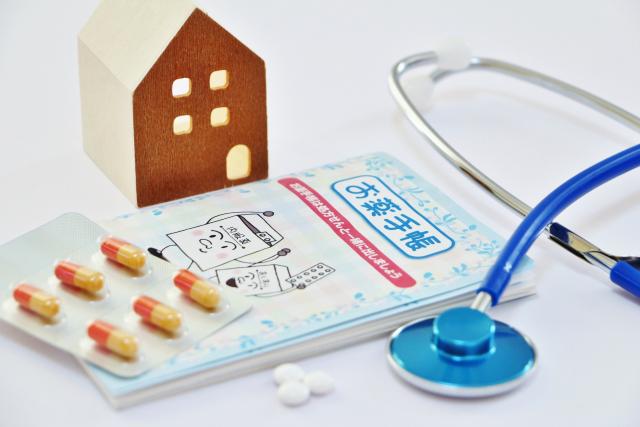 薬と手帳と家の模型
